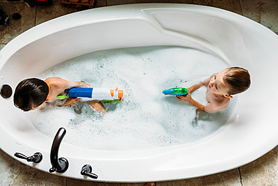 Overhead view of brothers playing with squirt gun in bathtub - p1166m1174179 by Cavan Images
