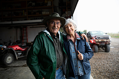Portrait happy, affectionate senior farmer couple in barn doorway - p1192m2109706 by Hero Images