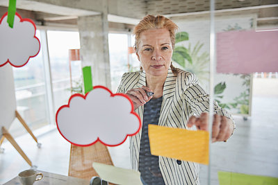 Businesswoman sticking adhesive notes on glass wall at office - p300m2265228 by Jo Kirchherr