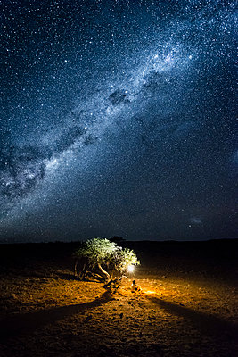 Tourist camping outdoor admiring the stars of the Southern Hemisphere, Namibia, Africa. - p651m2033368 by Marco Bottigelli