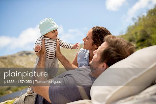 Familie mit Baby entspannt sich am Seeufer - p1355m1574053 von Tomasrodriguez