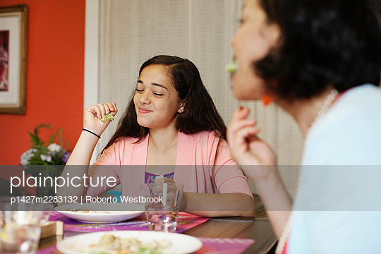 Mother and daughter having meal together - p1427m2283132 by Roberto Westbrook