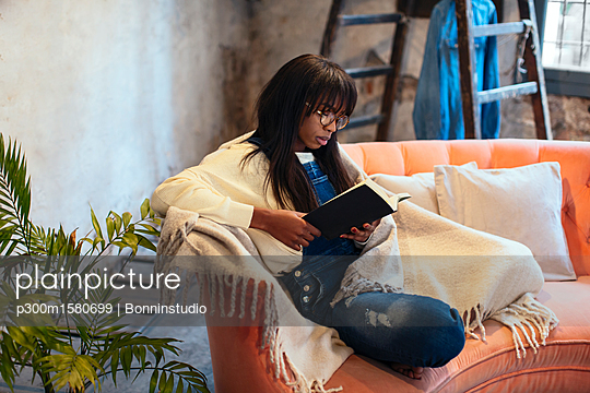 Young woman sitting on the couch at home reading book - p300m1580699 by Bonninstudio