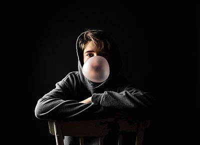 Teen boy in hoodie sitting on a chair in dark room blowing a bubble. - p1166m2191926 by Cavan Images