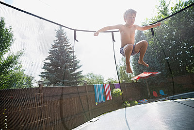 Boy jumping on trampoline in sunny backyard - p1192m1184059 by Hero Images