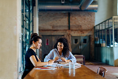 Two young businesswomen talking at conference table in loft office - p300m2144436 by Sofie Delauw