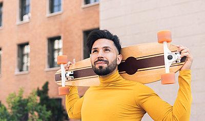 Thoughtful man with skateboard on shoulders - p300m2300084 von Jose Carlos Ichiro