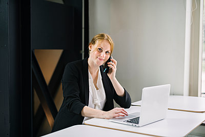 Woman in office talking via cell phone - p312m2191170 by Madeleine Wejlerud