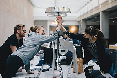 Happy female computer programmers giving high-five over desk in office - p426m1493887 by Maskot