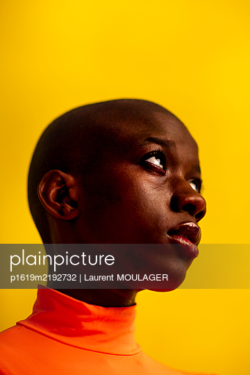 Portrait of a young bald woman in front of yellow background looking sideways - p1619m2192732 by Laurent MOULAGER