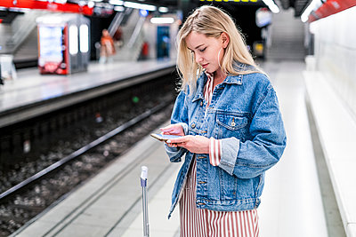 Spain, Barcelona, young blond woman standing at underground station platform looking at cell phone - p300m2069907 by Giorgio Fochesato