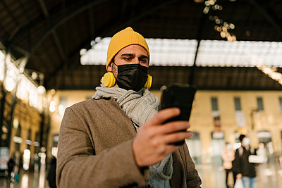 Man wearing protective face mask and knit hat using mobile phone while standing at station - p300m2251058 by Ezequiel Giménez