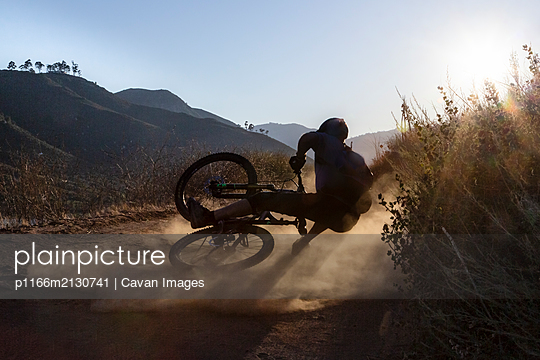 Mature man falling with mountain bike on trail in San Diego, CA - p1166m2130741 by Cavan Images