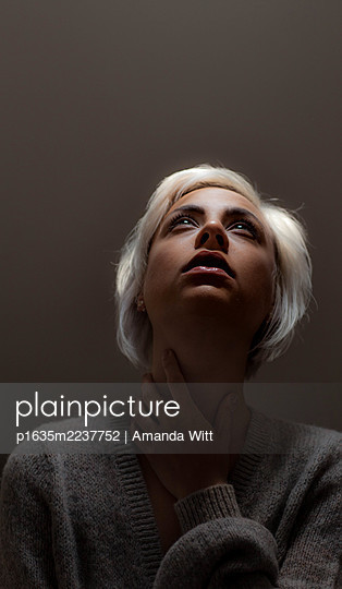 Young woman looking up, portrait - p1635m2237752 by Amanda Witt
