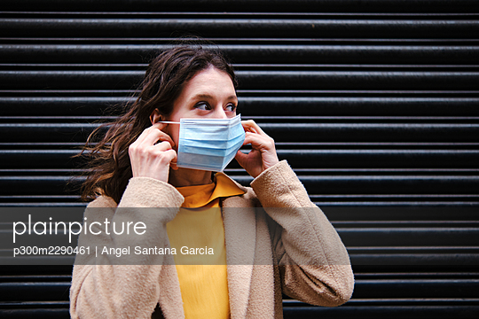 Woman looking away while wearing protective face mask in front of shutter during COVID-19 pandemic - p300m2290461 by Angel Santana Garcia