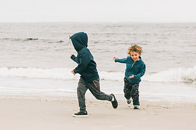 Happy brothers playing at beach against sky - p1166m1521013 by Cavan Images