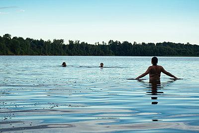 Female friends swimming in lake against sky - p1166m2025276 by Cavan Images