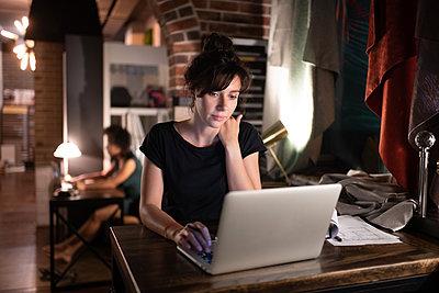 Smart designer using laptop in studio - p1166m2227673 by Cavan Images