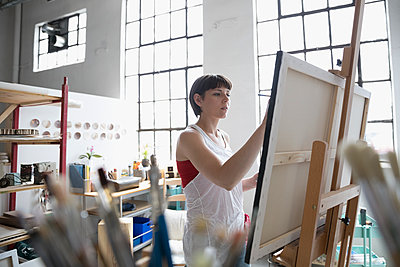 Female painter painting at canvas on easel in art studio - p1192m1490235 by Hero Images