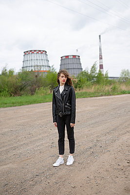Woman in front of a power plant - p1646m2278709 by Slava Chistyakov