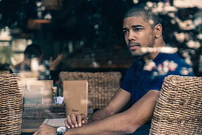 Man in a cafe behind windowpane - p300m1101113f by Zeljko Dangubic