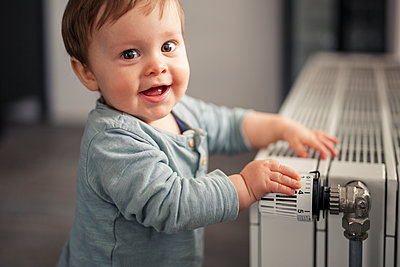 Portrait of smiling baby boy playing with thermostat of heater - p300m2084077 by Sebastian Dorn