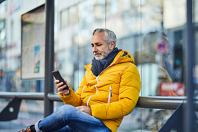Mature man using cell phone in the city - p300m2167194 by Jo Kirchherr