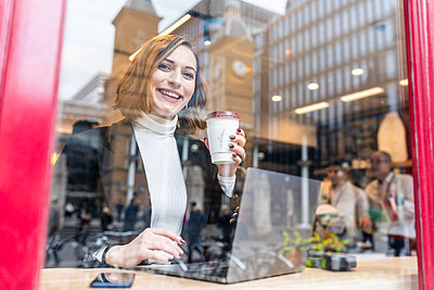 Portrait of happy businesswoman using laptop at a cafe in the city - p300m2180762 by William Perugini