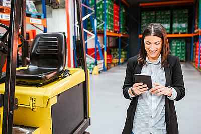 Smiling businesswoman using digital tablet by forklift in distribution warehouse - p300m2267045 by DREAMSTOCK1982
