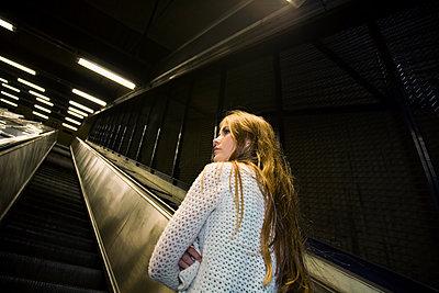 Sweden, Stockholm, Teenage girl (16-17) on escalator - p352m1126650f by Lena Katarina Johansson