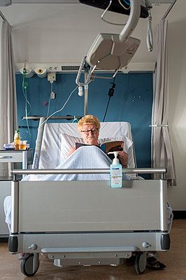 Patient in hospital bed reading magazine - p429m1198185 by Arno Masse