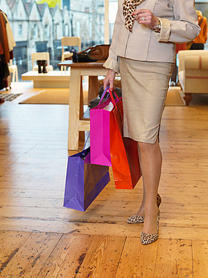Glamorous senior woman with shopping bags in boutique - p429m895368f by Colin Hawkins