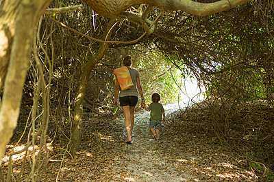 Caucasian mother and son walking on path - p555m1522936 by Marc Romanelli