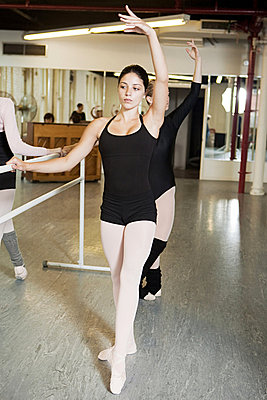 Ballerinas exercising at bar - p9245533f by Image Source