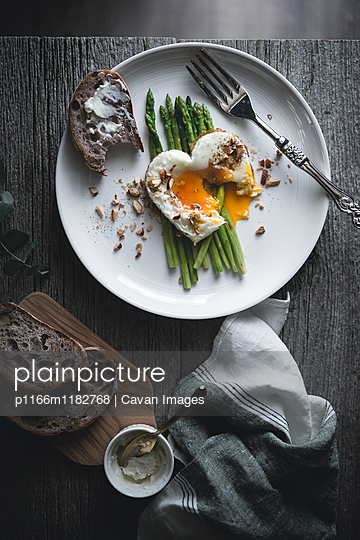 Overhead view of fried egg with asparagus and bread served in plate - p1166m1182768 by Cavan Images