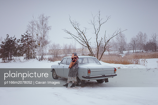 woman stands near the car in the winter in nature - p1166m2078052 by Cavan Images