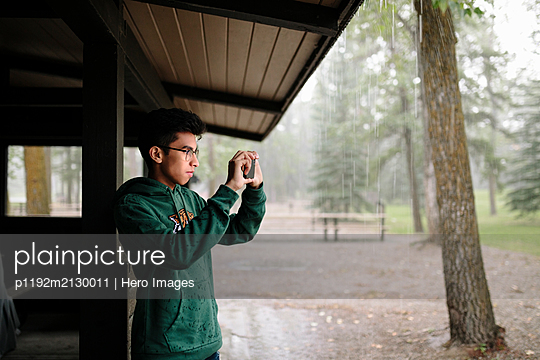Indian teenager taking photo on smartphone - p1192m2130011 by Hero Images