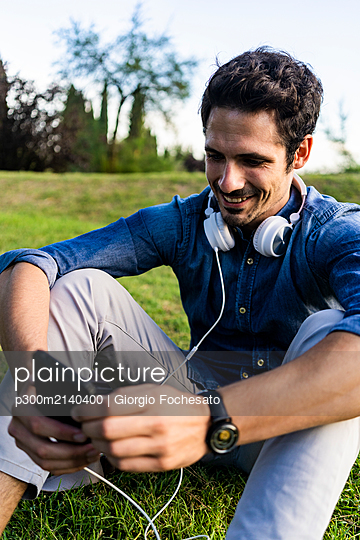 Smiling man sitting on a meadow using his smartphone - p300m2140400 by Giorgio Fochesato