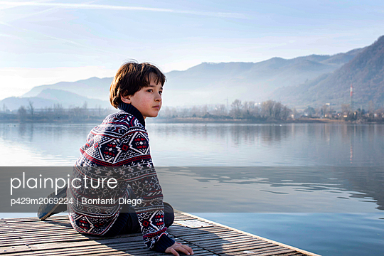Boy looking back from lakeside pier,  Lake Como, Lecco, Lombardy, Italy - p429m2069224 by Bonfanti Diego