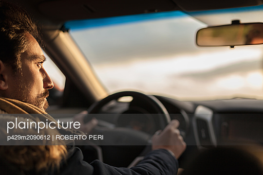 Man behind wheel at sunset - p429m2090612 by ROBERTO PERI