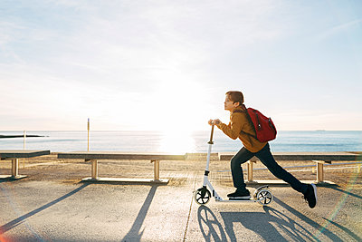 Boy riding scooter on beach promenade at sunset - p300m1562968 by Bonninstudio
