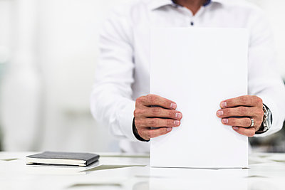 Man in office holding papers, Stockholm, Sweden - p312m894951f by Johner