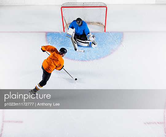 Hockey player shooting the puck at goal net
