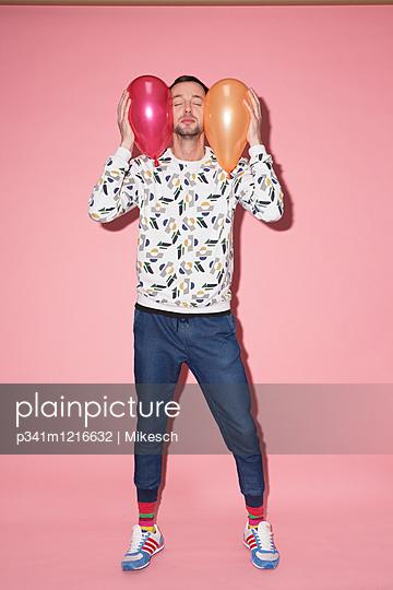 Junger Mann mit zwei Luftballons - p341m1216632 von Mikesch