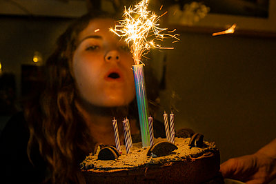 Young woman blows out candle on cake, stay at home due to Covid-19 - p1057m2185209 by Stephen Shepherd