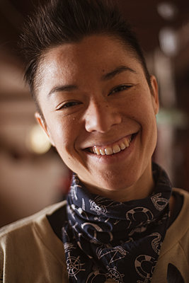 happy smiling queer asian woman inside warm cottage in czech republic - p1166m2290230 by Cavan Images