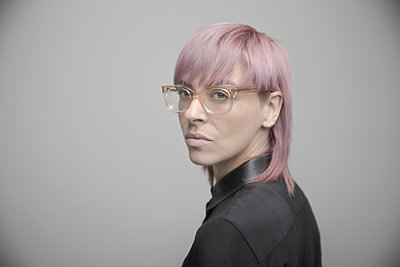 Portrait confident beautiful non-binary gender person with pink hair and eyeglasses - p1192m2066245 by Hero Images