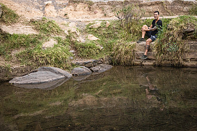 Hiker takes a break on the riverbank - p1640m2261055 by Holly & John
