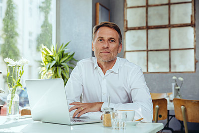 Portrait of businessman in cafe with laptop - p300m1505456 by Mareen Fischinger