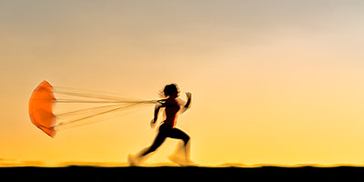 Silhouette young woman running with parachute during sunset - p300m2199530 by Stefan Schurr